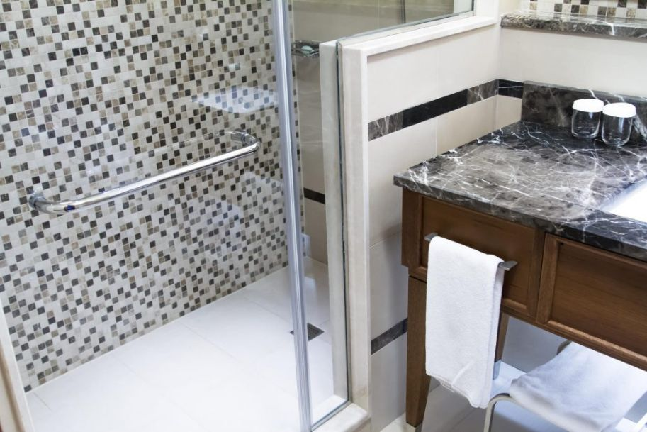 Shower tile installers Miami crew is one of the highest in demand. On this image you see a brand new tile installation for our client in Miami. The new bathroom sink and the shower tile was installed. The choice of gray color was selected by our client. The image was taken in March 2021