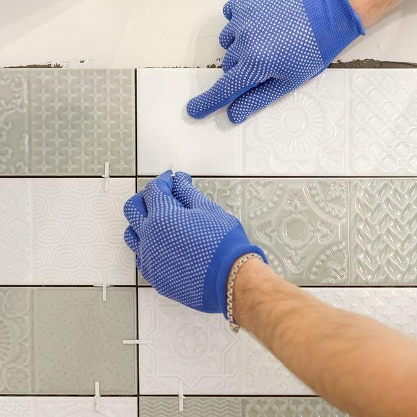 On this image you see a tile installer Miami specialist installing the backsplash tile as bathroom tile remodeling project. The project was taking place in Miami of 2021. The colors of gray and white were the choice for the tile installation.